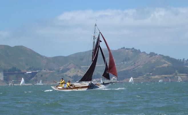 Gaff-rigged sloop Mercy blasting across the bay