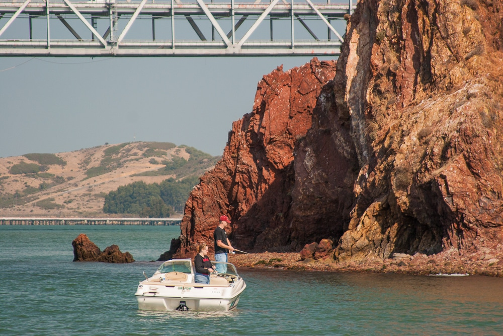 Two People Fishing Beside Red Rock Island