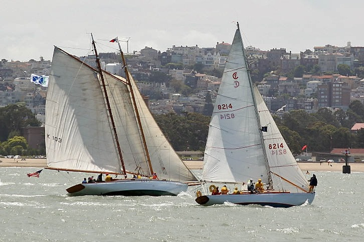 Two Sailboats Race Near Beach